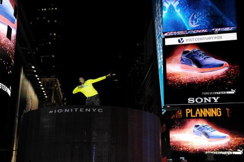 Usain Bolt přichází...svým typickým gestem ukazuje na boty.
